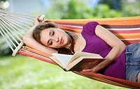 Young woman reading a book in a hammock