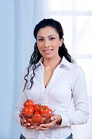 Young woman holding tomatoes in bowl, portrait