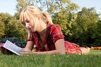 Young blond woman reading book in grass