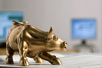 Bull figurine on newspaper, background computers, close_up