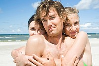 two girls hugging boy on beach
