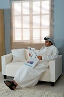 Arab man reading newspaper, sitting on a sofa
