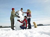 Family with Dog Building Snowman