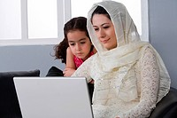 Arab mother and daughter with laptop sitting in the living room