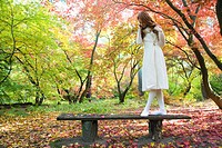 Young woman standing on park bench