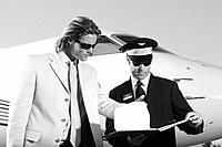 Businessman and Pilot Looking over Paperwork