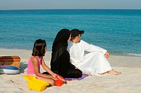 Girl sitting with parents on beach, side view