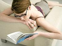 Woman Lying on Couch Reading Book
