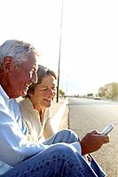 Elderly Couple with Mobile Phone Sitting at the Roadside