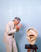 Businessman Shouting Into Big Ear