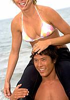 Woman on Man's Shoulders at Beach