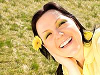 smiling woman with flower in the garden