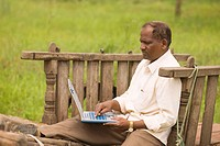 Educated farmer working on laptop computer in bullock cart , village Salunkwadi , Taluka Ambajogai , District Beed , Maharashtra , India MR688