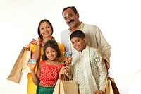 South Indian parents and children holding shopping bags showing credit cards MR748S,748T,748U,748V