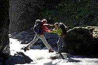 Two Hikers Crossing Mountain Stream
