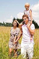 portrait of young family walking through meadow