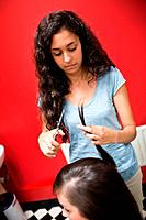 Portrait of a young female hairdresser cutting hair with scissors