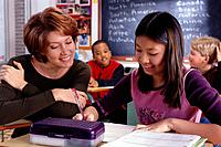 Teacher Helping Girl with Classwork
