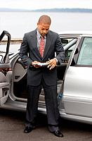 Ethnic Business Man with clipboard and pen next Luxury Car