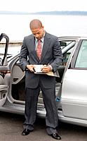 Ethnic Business Man Writing Left Handed on Clipboard