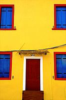 A bright yellow facade with blue window shutters.