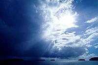 Sun rays pierce an immense storm descending over tropical islands.