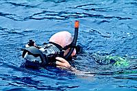 A man snorkels on the ocean surface with an underwater camera.