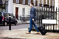 A young man pulling his suitcase in the street (thumbnail)