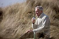 A senior man sitting amongst the sand dunes, having a hot drink (thumbnail)