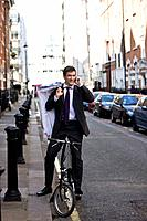 A businessman on his bicycle, talking on his mobile phone (thumbnail)