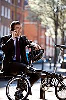 A businessman sitting on a bench, talking on his mobile phone