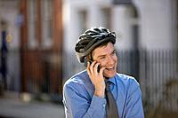 A businessman on his bicycle, talking on his mobile phone