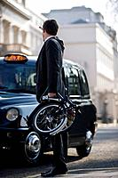 A businessman hailing a taxi, holding his folded bicycle