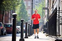 A young man jogging in the street, listening to music