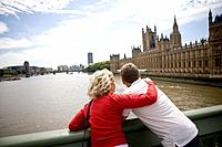 A middle_aged couple standing near the Houses of Parliament, looking along the river Thames