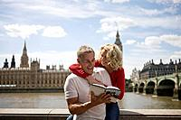 A middle_aged couple in front of the Houses of Parliament, looking at a guidebook