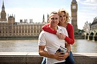 A middle_aged couple in front of the Houses of Parliament, holding a guidebook