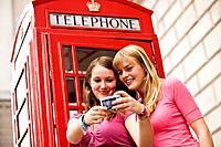 Two teenage girls taking a photograph of themselves in front of a telephone box