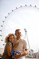 A middle_aged couple standing in front of the London Eye