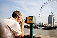 A middle_aged man using a telescope in front of the London Eye