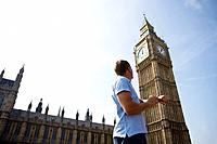 A middle_aged man checking his watch next to Big Ben