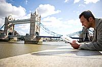 A mid_adult man standing near Tower Bridge, looking at a guidebook
