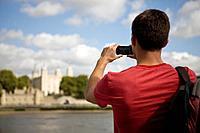 A mid_adult man taking a photograph of the Tower of London