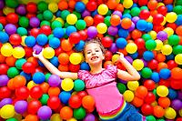 Child girl playing on colorful balls playground high view