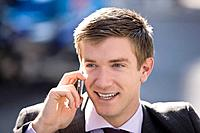 Portrait of a businessman talking on a mobile phone, outside