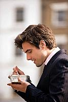 A businessman standing in the street, eating take_away food