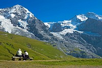 wanderes sitting on bench, Moench and Jungfrau mountain tops in background, Switzerland, Berne, Bernese Oberland, Kleine Scheidegg