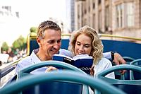 A middle_aged couple sitting on a sightseeing bus, looking at a guidebook