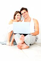 Portrait of a sweet young couple using laptop while sitting on the floor