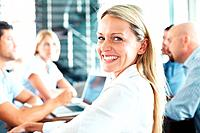 Portrait of cheerful young businesswoman in a business meeting smiling with colleagues at the back